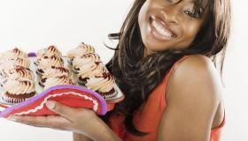 African American woman holding cupcakes