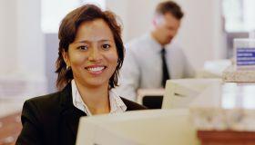 Bank teller smiling, sitting behind computer, portrait