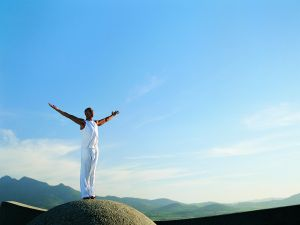Man Standing on Boulder With Arms Outstretched