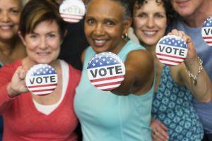 Senior friends holding Vote' buttons