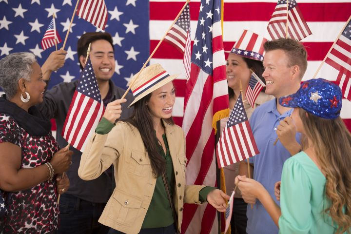 Multi-ethnic group. American people at political rally. USA flags. Voting.