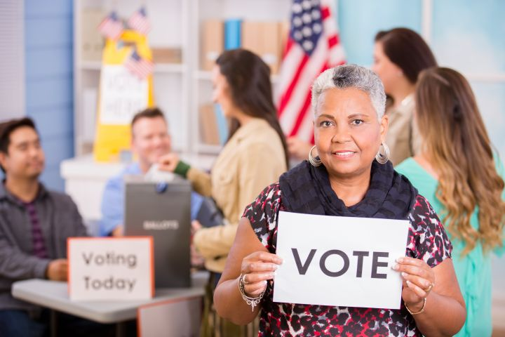 Voters register, voting in USA elections. Woman holds 'Vote' sign.