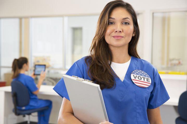 Nurse wearing Vote button in hospital
