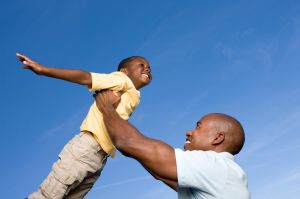 Father lifting son, son pretending to fly
