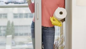 Woman cleaning door, smiling, portrait