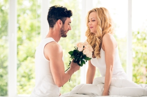 Man gives bouquet of roses to woman