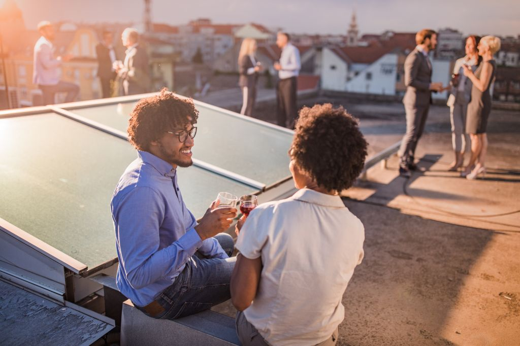 Happy African American man toasting with his female colleague during a party on a roof.