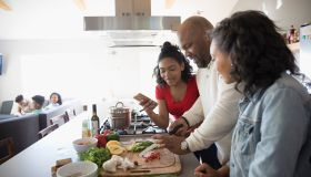 African American father and daughters cooking in kitchen