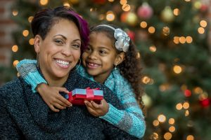 A mother and daughter are opening presents together