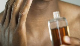 African man applying cologne