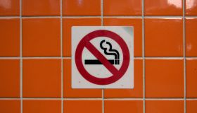'No smoking' sign on a wall with glossy orange tiles