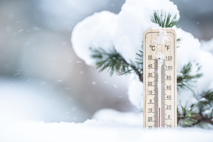 Thermometer in the snow shows low temperatures in Celsius and Farenhaits.